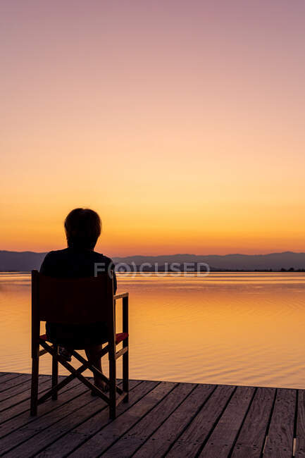 Silhouette of person from behind sitting on chair on wooden pier against bright orange sunset sky above water — Stock Photo