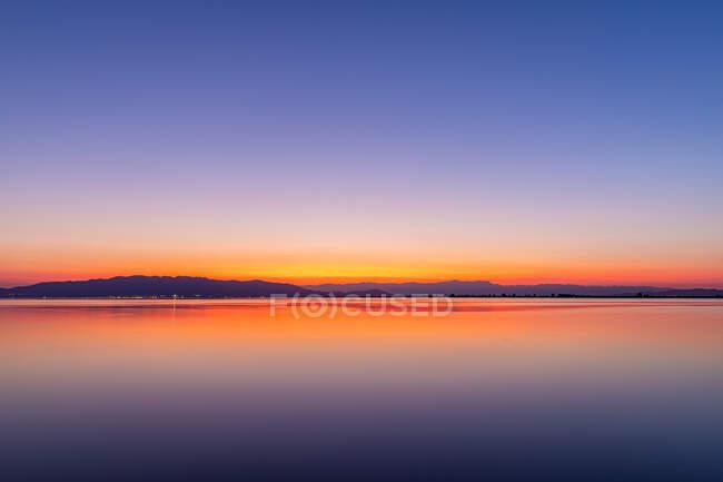 Colores intensos de una puesta de sol con reflejos en el agua - foto de stock