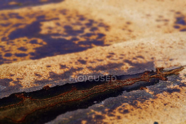 Closeup of weathered iron surface with corrosion spots and remaining old paint — Stock Photo