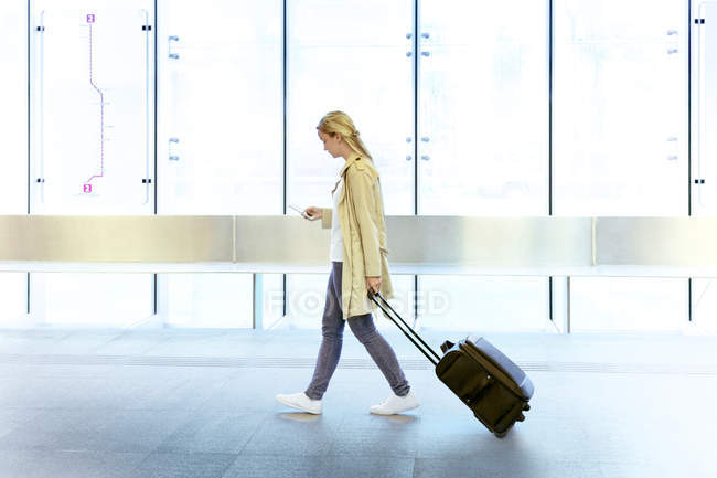 Side view of young female tourist in casual wear using smartphone while walking in airport with wheeled suitcase — Stock Photo