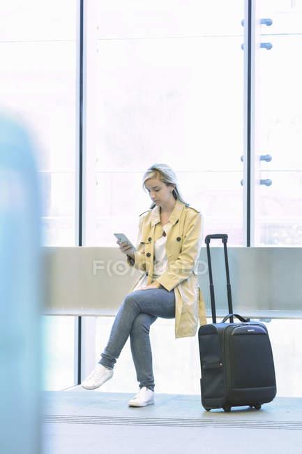 Junge blonde Touristin benutzt Smartphone, während sie mit Gepäck am Flughafen sitzt — Stockfoto