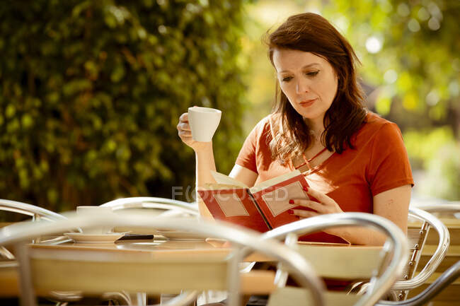 Adult tranquil concentrated lady reading book and drinking tea while sitting on cozy summer cafe terrace and enjoying sunny day — Stock Photo