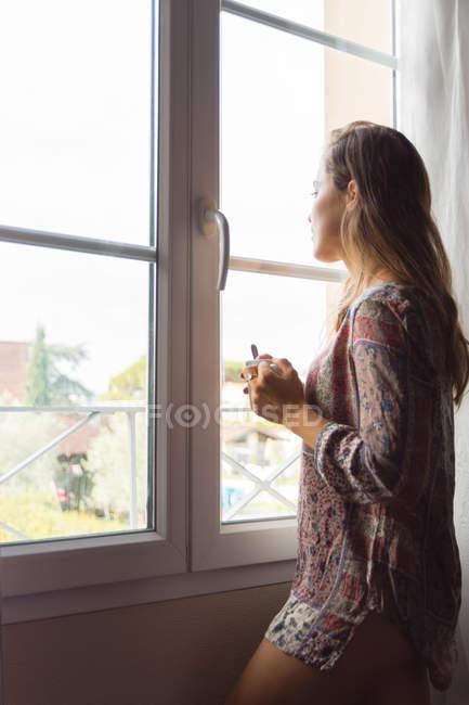Ragazza bionda pensosa in camicia con una tazza di caffè che guarda fuori le finestre al mattino — Foto stock