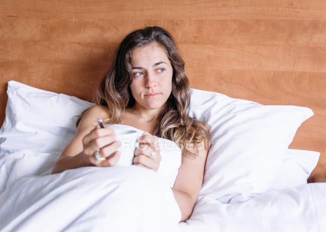 Sorrindo menina loira segurando uma xícara de café em uma cama de manhã olhando para longe — Fotografia de Stock