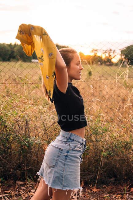 Вид на содержание бронзовой женщины в повседневной одежде снимая рубашку возле металлической цепи звено забора на сельском поле — стоковое фото