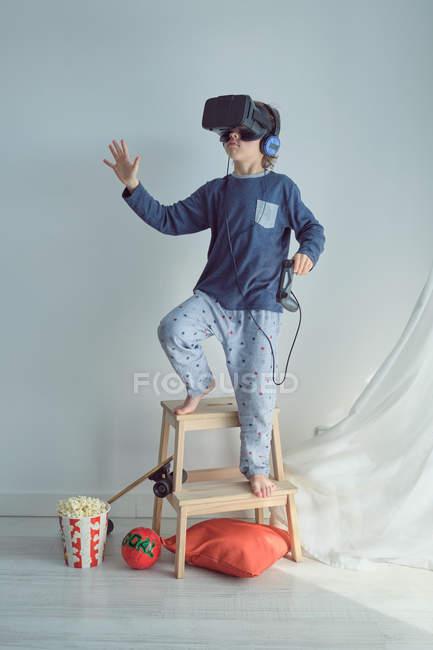 Niño alegre en pijama azul con gafas VR mientras disfruta de juegos virtuales en casa - foto de stock