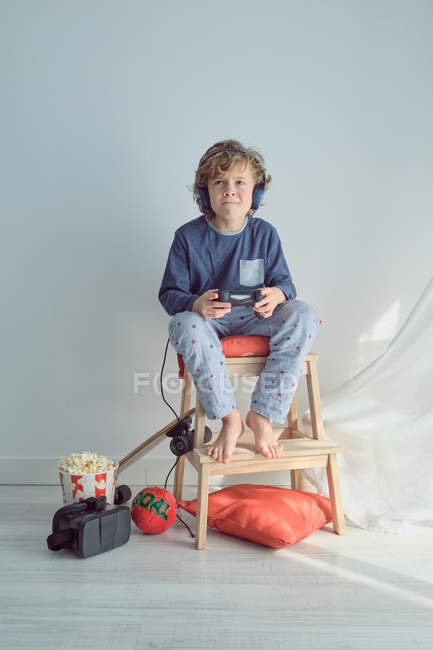 Competitive kid in pajama and headphones and playing games while sitting on chair and looking at camera making faces — Stock Photo