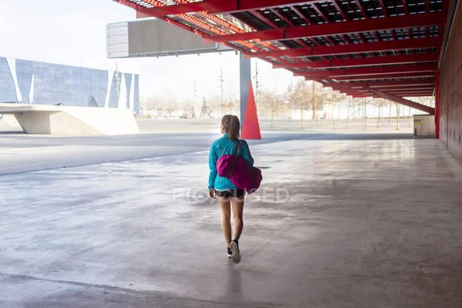 Sportswoman holding bag while walking away - foto de stock