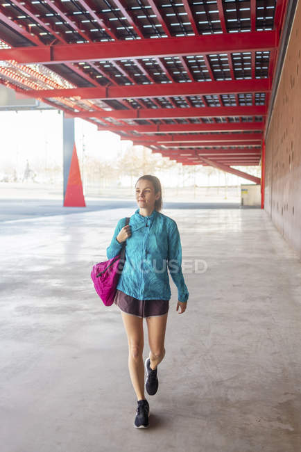 Sportswoman holding bag while walking in the streets - foto de stock