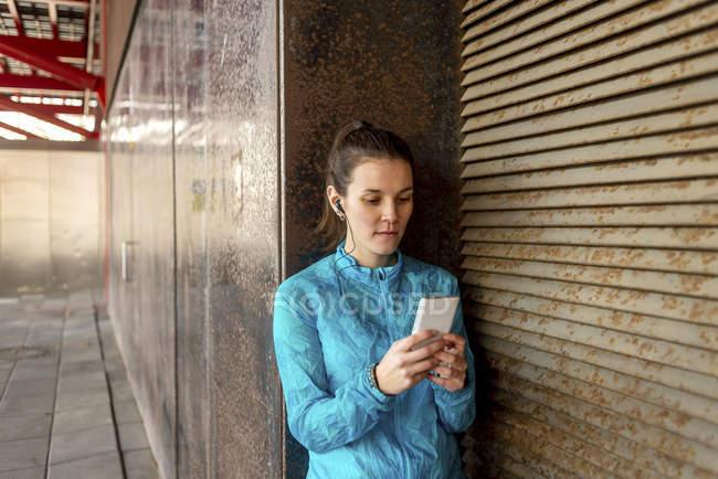 Porträt der schönen Sportlerin mit Handy — Stockfoto
