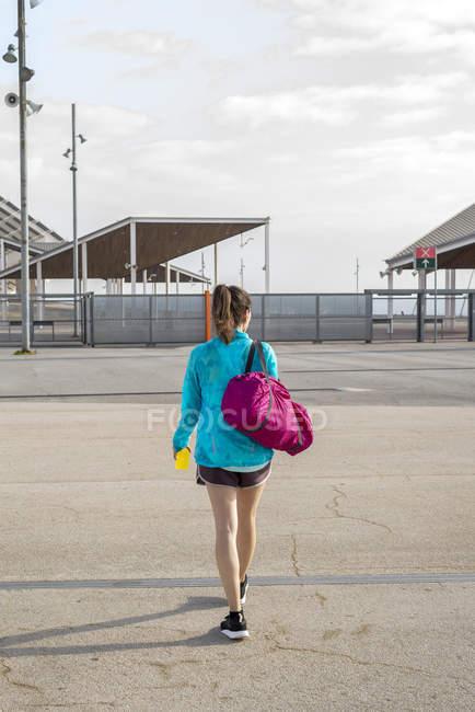 Back view of Sportswoman holding bag while walking away - foto de stock