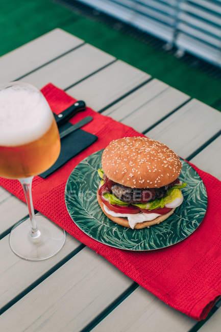 Вкусный домашний чизбургер с салатом, помидорами и соусом на зеленой тарелке, подаваемый со стаканом пива . — стоковое фото