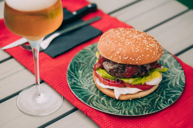 Delicious homemade beef burger with lettuce, tomato and sauce on green plate served with glass of beer. — Stock Photo