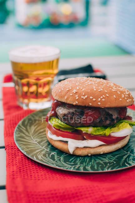 Вкусный домашний гамбургер с салатом, помидорами и соусом на зеленой тарелке, подаваемый со стаканом пива . — стоковое фото