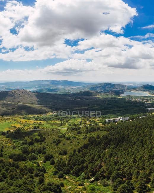 Paysage époustouflant de collines de pierre couvertes d'herbe sèche sous de gros nuages blancs et moelleux sur le ciel — Photo de stock