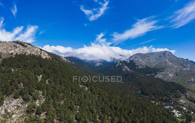Aerial view of beautiful landscape, blue cloudy sky and lakes surrounded by forests and mountains — Stock Photo