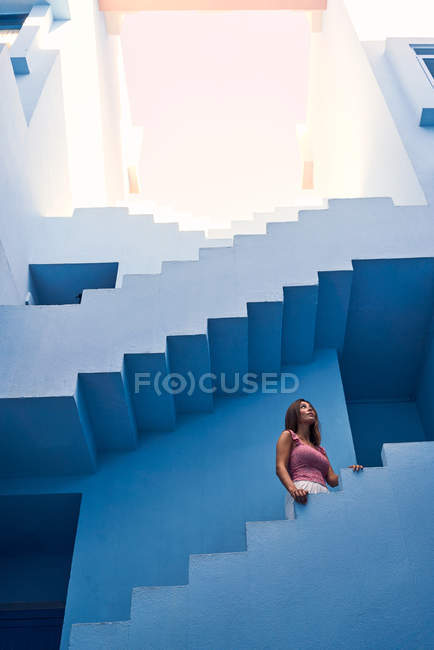 Side view of woman walking upstairs on modern blue building and looking up — Stock Photo