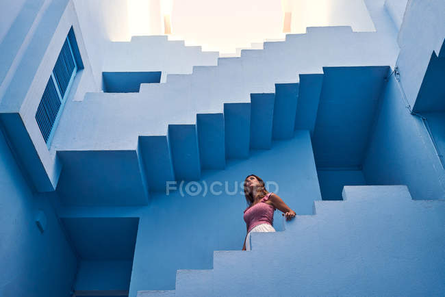 Side view of woman walking downstairs on modern blue building — Stock Photo