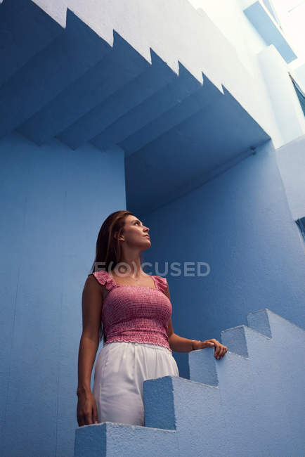 Side view of woman walking upstairs on modern blue building and looking up — Foto stock