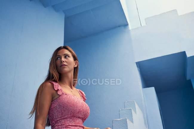 Вид сбоку на женщину, идущую вверх по современному синему зданию и отводящую взгляд — стоковое фото