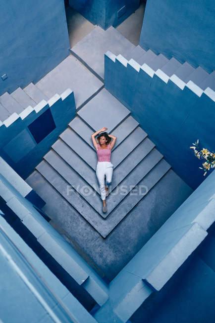 Вид сверху на женщину, лежащую на синей лестнице здания — стоковое фото