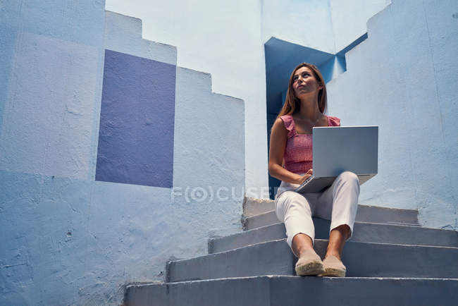 Beautiful woman sitting on blue staircase of blue building and using computer — Stock Photo