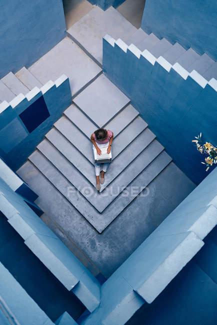 Vista superior da mulher bonita sentada na escada azul do edifício azul e usando o computador — Fotografia de Stock