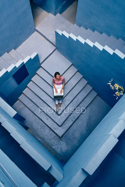 Top view of Beautiful woman sitting on blue staircase of blue building and using computer — Stock Photo