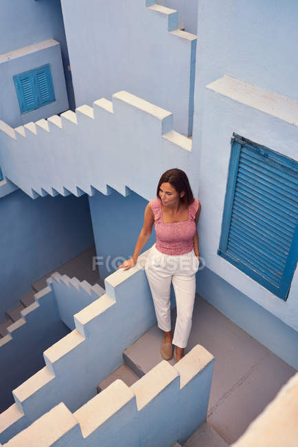 Top view of young woman walking upstairs on modern blue building and looking away — Stock Photo