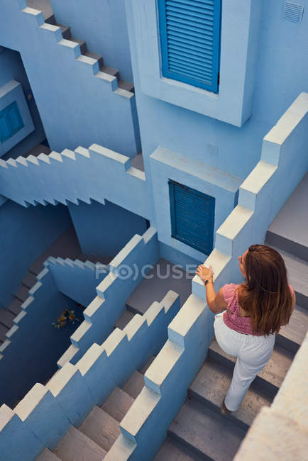 De cima vista da jovem mulher andando no andar de cima no edifício azul moderno e olhando para longe — Fotografia de Stock