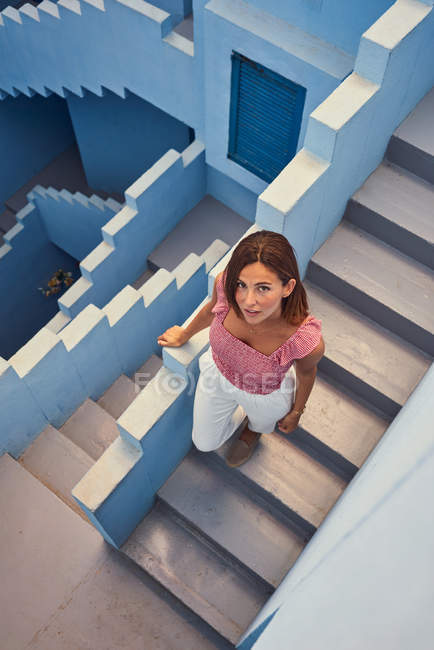 From above view of young woman walking upstairs on modern blue building and looking at camera — Stock Photo