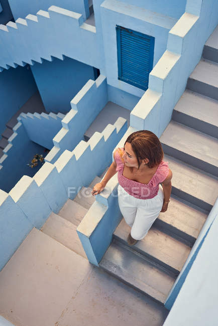 From above view of young woman walking upstairs on modern blue building and looking away — Stock Photo