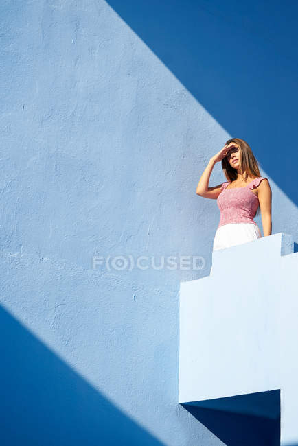Woman standing on top of blue building with closed eyes — Stock Photo