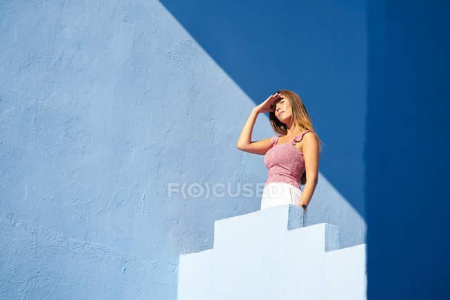 Frau steht auf blauem Gebäude und schaut weg — Stockfoto