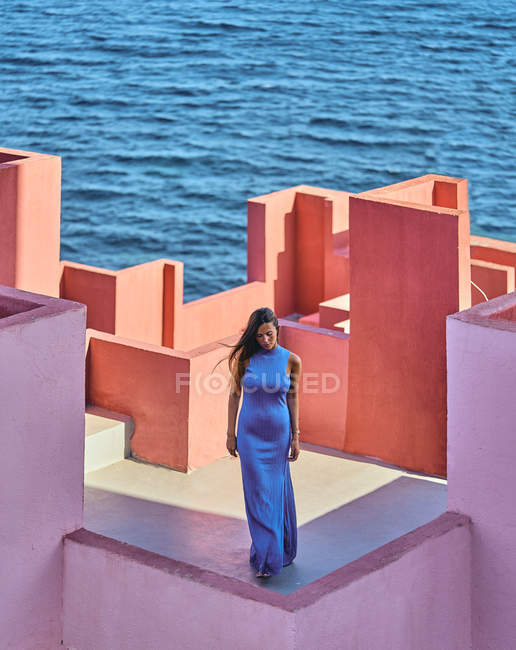Woman in blue dress standing on roof of building — Stock Photo