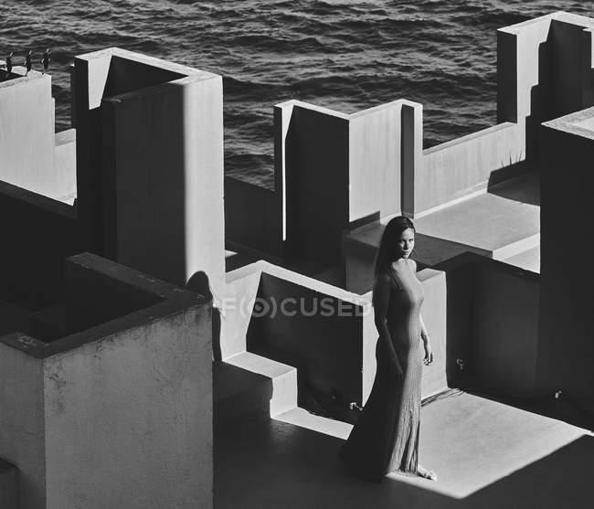Mulher de vestido em pé no telhado do edifício — Fotografia de Stock