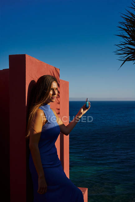 Beautiful woman in blue dress leaning on red wall building, holding cosmetic bottle — Stock Photo