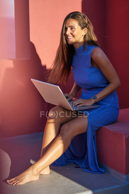 Beautiful barefoot woman in blue dress sitting on step of red building and using laptop — Stock Photo