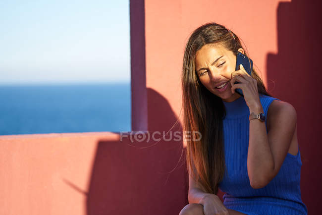 Beautiful happy woman sitting on step of red building and talking by smartphone — Foto stock