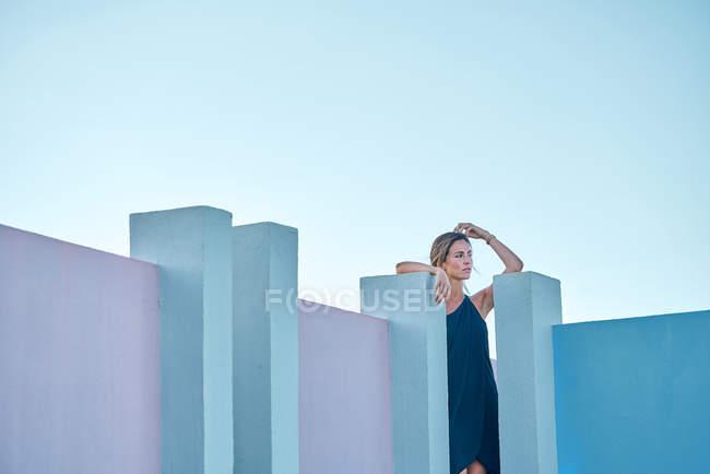 Жінка стоїть зверху синього будинку і дивиться на камеру. — стокове фото