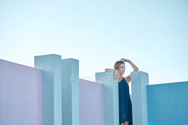 Woman standing on top of blue building and looking at camera — Stock Photo