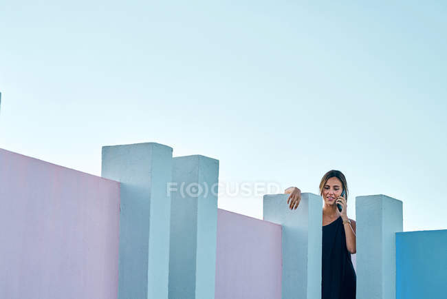 Woman standing on top of blue building and talking by smartphone — Foto stock