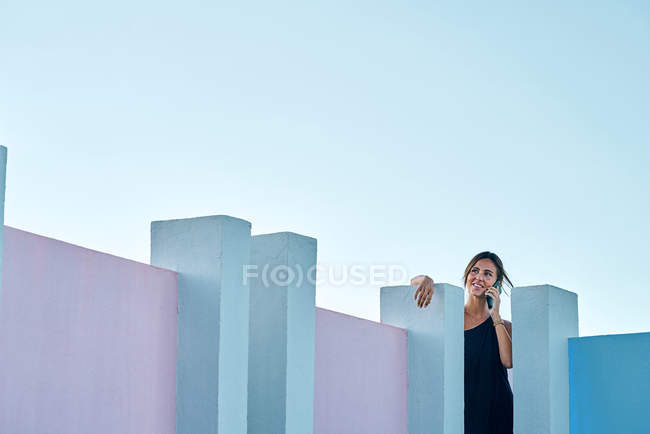 Woman standing on top of blue building and talking by smartphone — Stock Photo