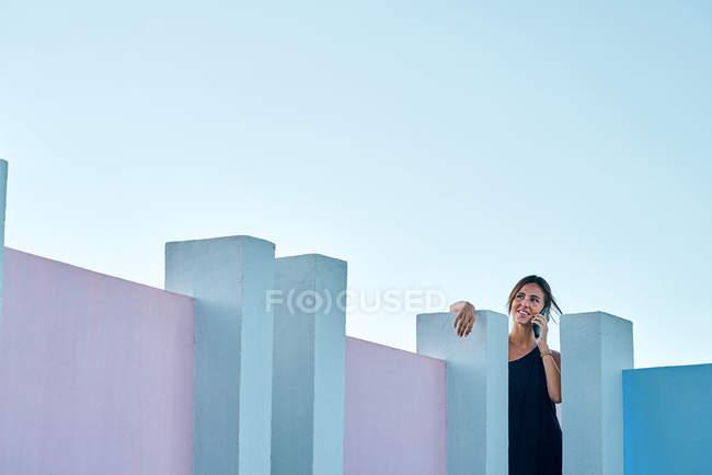 Femme debout sur le dessus du bâtiment bleu et parler par smartphone — Photo de stock