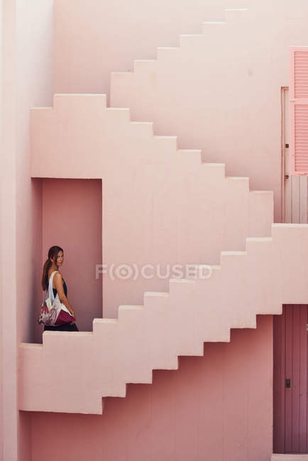 Side view of woman walking downstairs on modern pink building while looking at camera — Foto stock