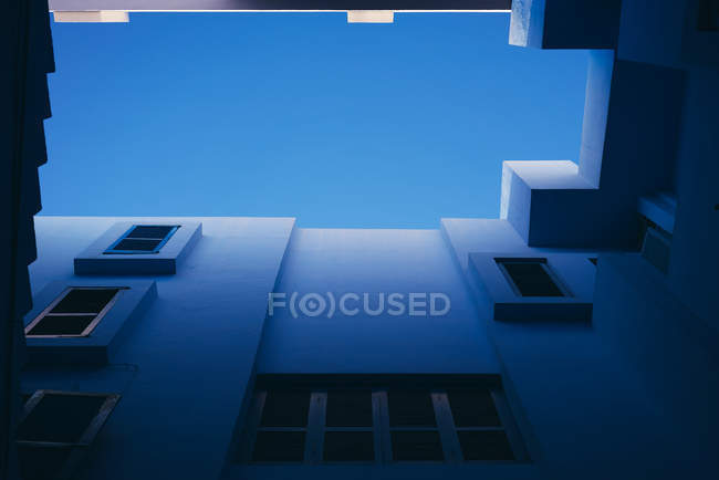 From below geometric windows in passage of building — Stock Photo