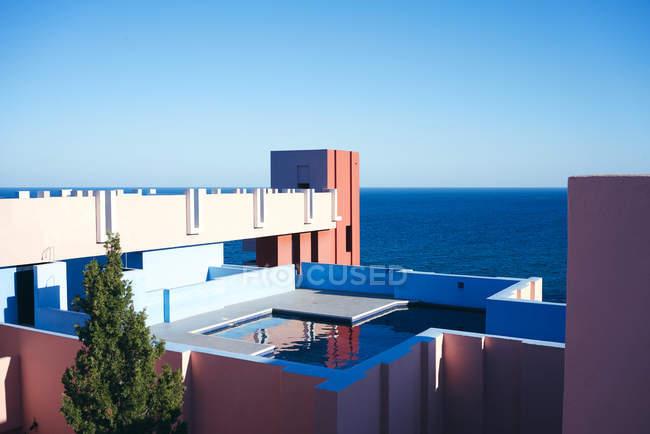 Удивительный бассейн с пресной водой, отражающей небо на крыше интересной формы здания в яркий солнечный день — стоковое фото