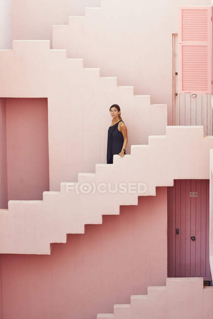 Side view of woman walking downstairs on modern pink building while looking away — Stock Photo