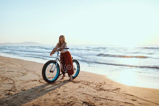 Donna allegra in bicicletta lungo la spiaggia tranquilla — Foto stock