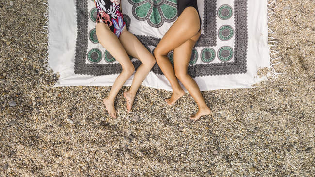Cropped image of two women in swimwear relaxing on blanket on seashore — Stock Photo